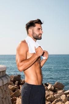 Hübscher sportiver mann, der pause nach intensivem training hat