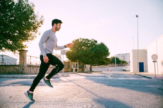 Hübscher sportler, der auf straße sprintet