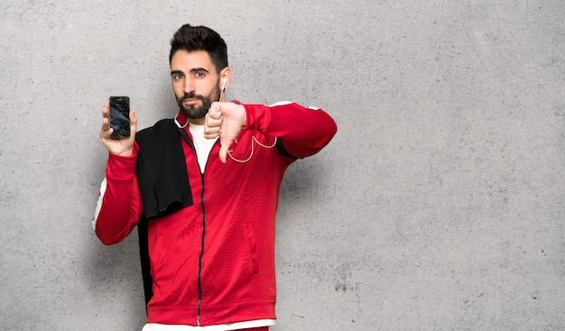 Hübscher sportler mit dem gestörten halten gebrochenen smartphone über strukturierter wand