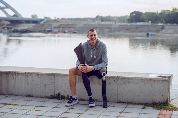 Hübscher sportlicher kaukasischer behinderter mann in sportbekleidung und mit künstlichem bein, das auf kai sitzt und ein anderes künstliches bein hält.