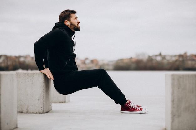 Hübscher sportlicher mann, der im park durch den fluss streckt