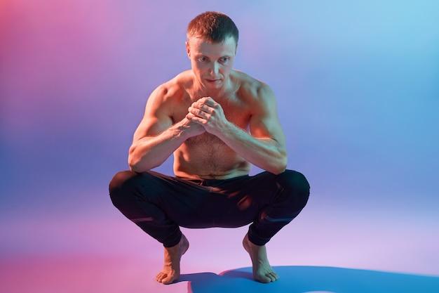 Hübscher sportlicher mann, der in yoga-asanas meditiert, hockt und auf beinen steht