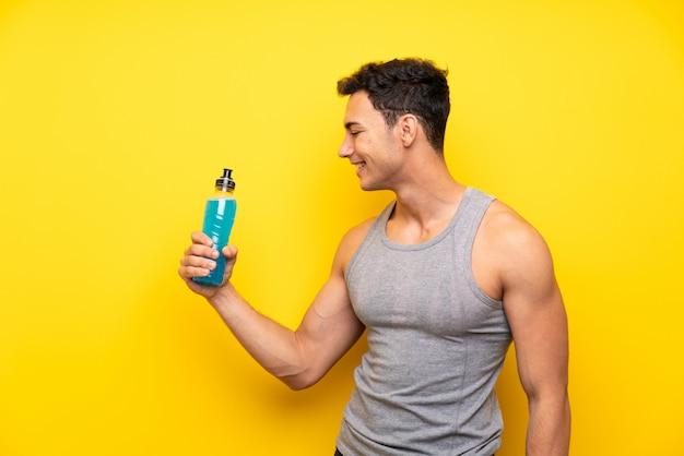 Hübscher sportmann mit einer flasche soda