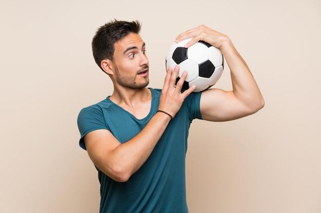 Hübscher sportmann über dem lokalisierten hintergrund, der einen fußball hält