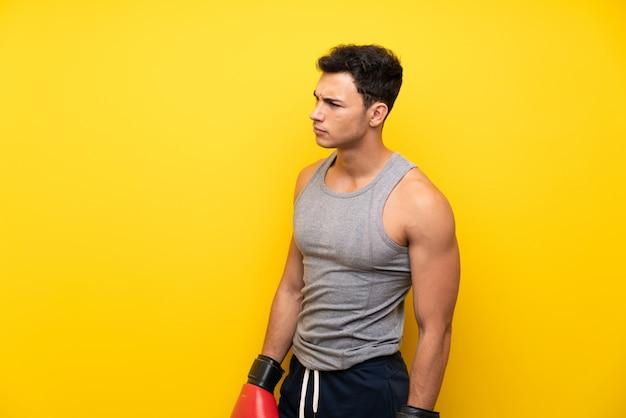 Hübscher sportmann über lokalisiertem hintergrund mit boxhandschuhen