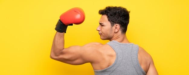 Hübscher sportmann über lokalisierter wand mit boxhandschuhen