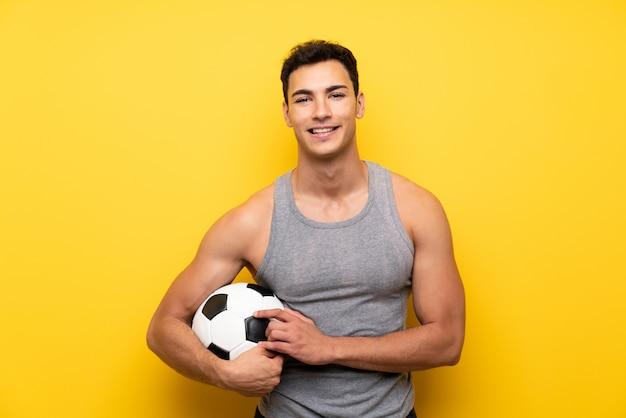 Hübscher sportmann über lokalisierter wand mit einem fußball
