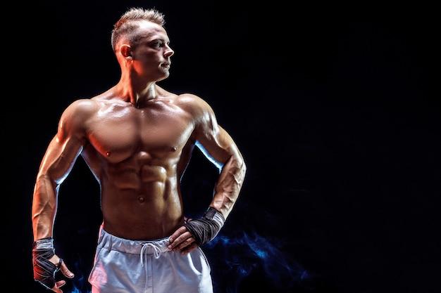 Hübscher starker bodybuilder, der im studio auf aufwirft