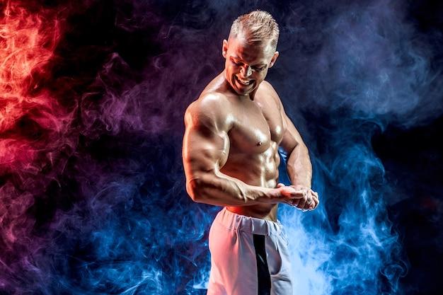 Hübscher starker bodybuilder, der im studio auf farbigem rauch aufwirft