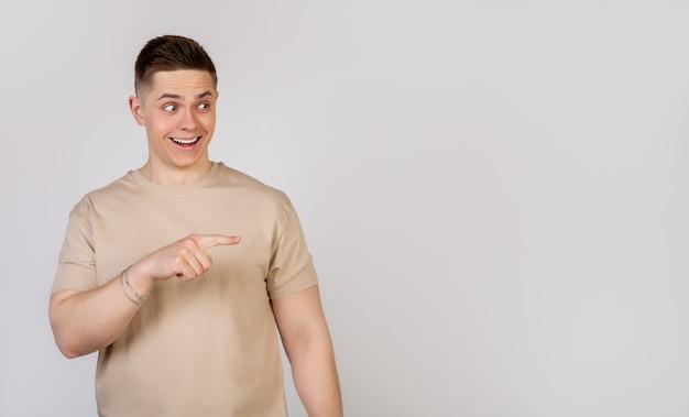 Hübscher starker junger mann, der finger mit einem überraschten ausdruck auf seinem gesicht nach rechts zeigt