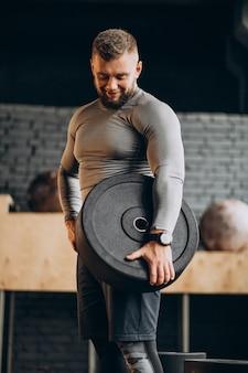Hübscher starker mann, der an der turnhalle trainiert