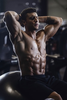 Hübscher starker mann, der muskeln an der turnhalle aufpumpt