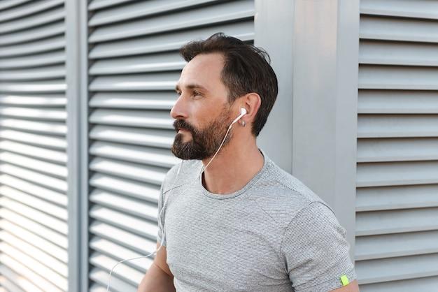Hübscher starker reifer sportler, der musik mit kopfhörern hört.