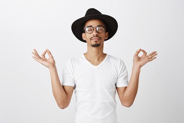 Hübscher stilvoller afroamerikaner kerl im hipsterhut und in der brille, die meditieren, praktizieren yoga