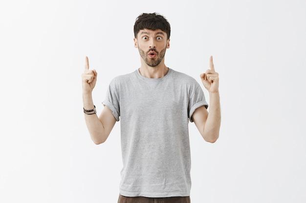Hübscher stilvoller bärtiger mann, der finger zeigt und wow überrascht sagt