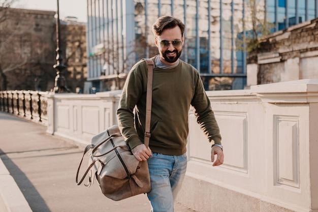 Hübscher stilvoller hipster-mann, der in der stadtstraße mit ledertasche geht, die sweatshot und sonnenbrille trägt, stadtstil-trend, sonniger tag, lächelnder glücklicher reisender