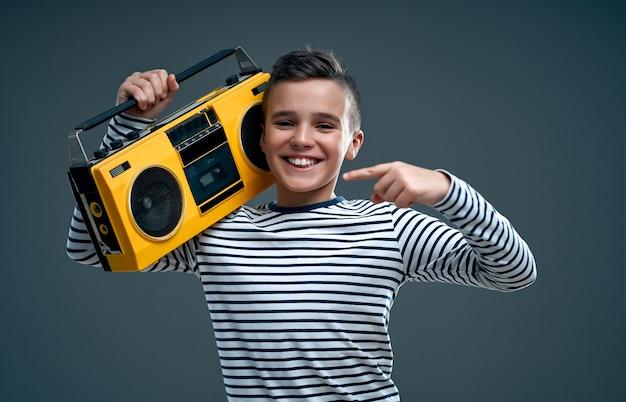 Hübscher stilvoller junge in einem gestreiften pullover mit einem gelben retro-tonbandgerät lokalisiert auf einem grau.