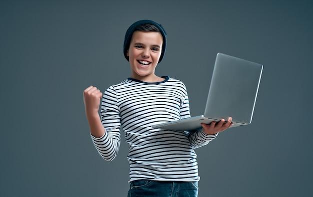Hübscher stilvoller junge in einem gestreiften pullover und hut mit einem laptop in der hand zeigt eine geste ja isoliert auf einem grau.
