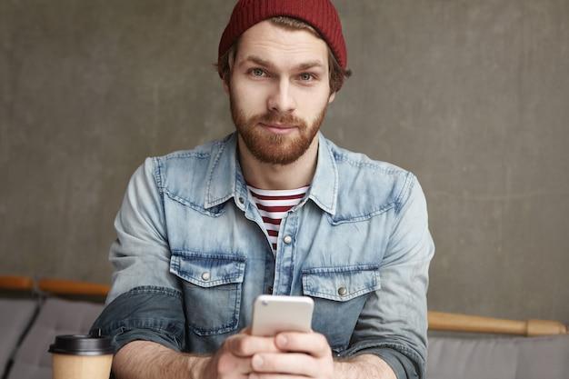 Hübscher stilvoller junger kaukasischer mann, der handy hält, seiner freundin eine sms sendet und sie bittet, an einem warmen frühlingstag einen spaziergang zu machen, während er im café sitzt und frischen kaffee in pappbecher genießt