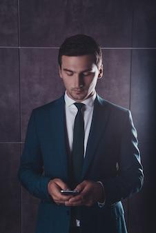 Hübscher stilvoller junger mann, der sms am telefon schreibt