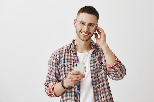 Hübscher stilvoller junger mann mit brille, die mit seinem telefon aufwirft
