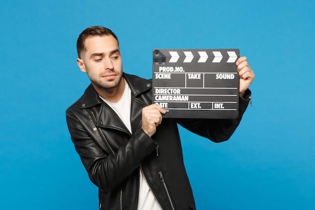 Hübscher, stilvoller junger unrasierter mann in schwarzer jacke, weißem t-shirt, der in der hand hält, um filmklappe zu machen, die auf blauem wandhintergrund studioporträt isoliert ist. menschen lifestyle-konzept. kopieren sie platz.