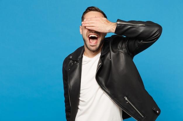 Hübscher, stilvoller junger, unrasierter mann in schwarzer lederjacke, weißem t-shirt, der kamera isoliert auf blauem wandhintergrund-studioporträt sieht. menschen aufrichtige emotionen lifestyle-konzept. mock-up-kopierraum Kostenlose Fotos