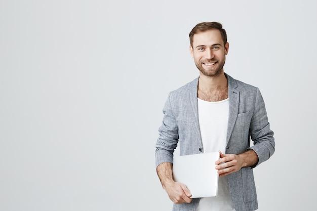 Hübscher stilvoller männlicher unternehmer mit laptop