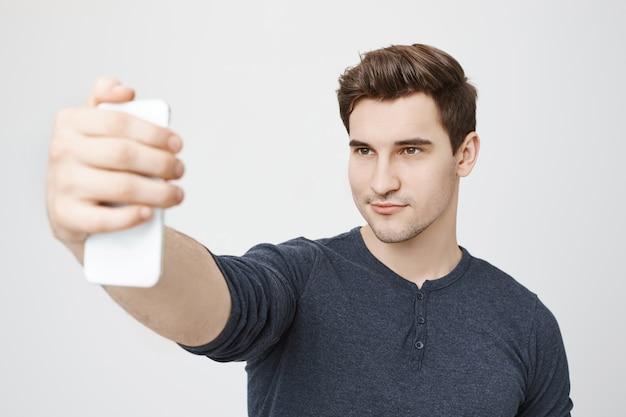 Hübscher stilvoller mann, der selfie für soziale medien auf smartphone nimmt