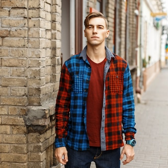 Hübscher stilvoller mann im modischen karierten hemd nahe der vintagen backsteinmauer
