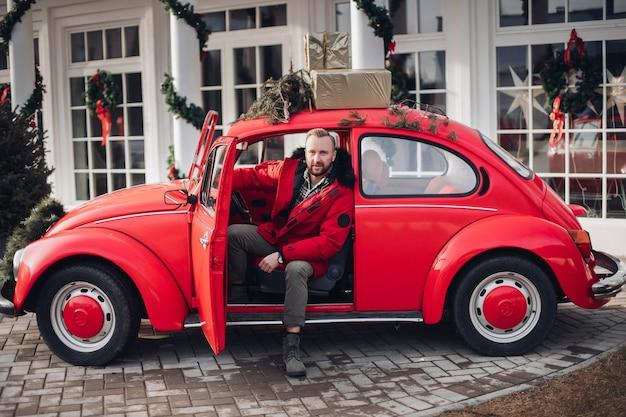 Hübscher stilvoller mann in der roten winterjacke, die im roten oldtimer mit weihnachtsgeschenken oben sitzt.