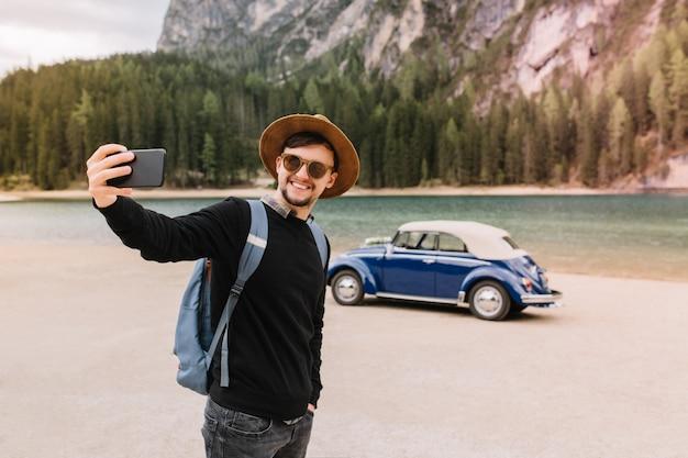 Hübscher stilvoller mann in der sonnenbrille, die entlang des seeufers geht und selfie mit italienischen alpen macht