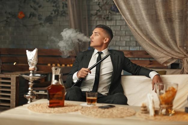 Hübscher stilvoller mann in einem anzug, der eine wasserpfeife raucht
