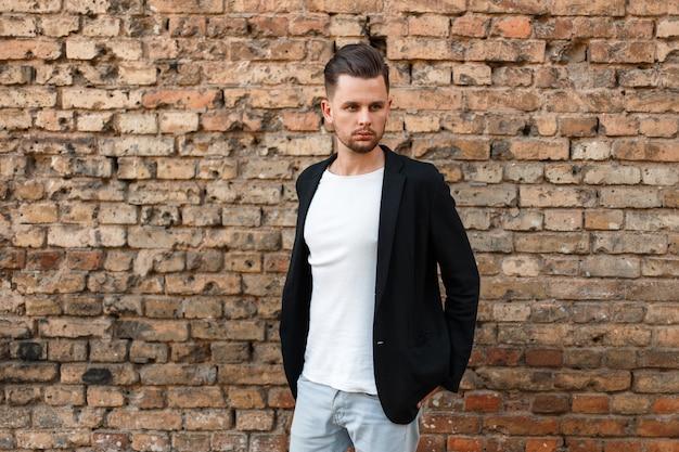 Hübscher stilvoller mann in einer schwarzen geschäftsjacke und einem weißen t-shirt, die nahe einer mauer aufwerfen