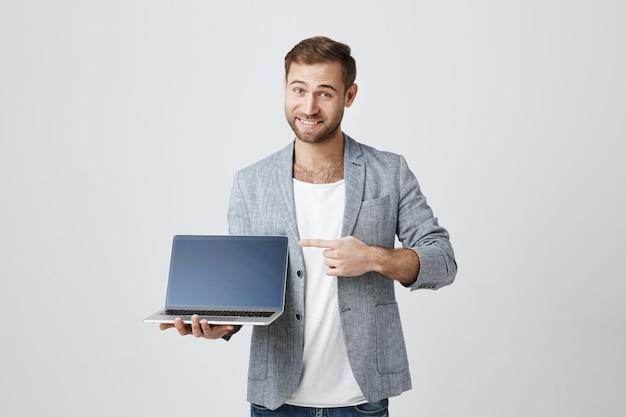 Hübscher stilvoller unternehmer, der auf laptop-anzeige zeigt