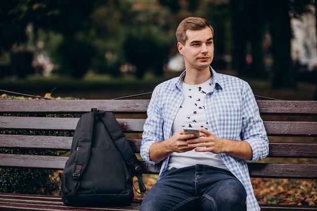 Hübscher student, der auf bank sitzt und telefon benutzt