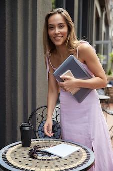 Hübscher student, der eine tasse kaffee außerhalb des cafés mit laptop und telefon trinkt