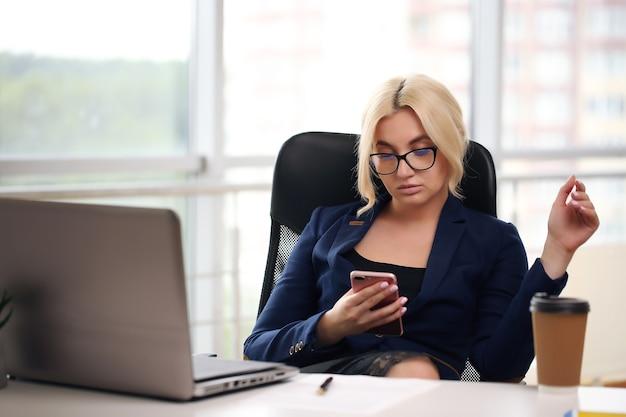Hübscher student im anzug, der am schreibtisch mit laptop sitzt.