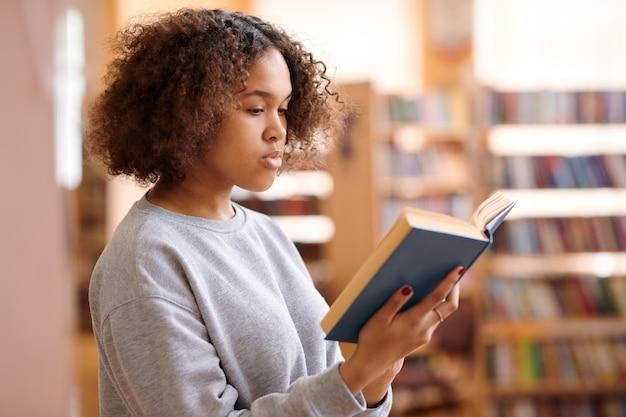 Hübscher student in der freizeitkleidung, der interessantes buch liest, während er universitätsbibliothek besucht