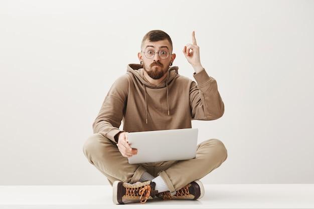 Hübscher student sitzt mit laptop auf gekreuzten beinen und hebt den zeigefinger, hat eine gute idee