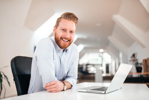 Hübscher tausendjähriger rothaarigemann, der an der kamera beim sitzen am schreibtisch mit laptop lächelt.