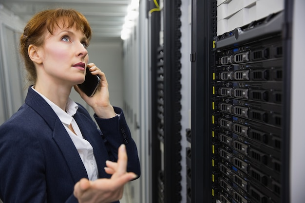 Hübscher techniker, der am telefon beim betrachten des servers spricht