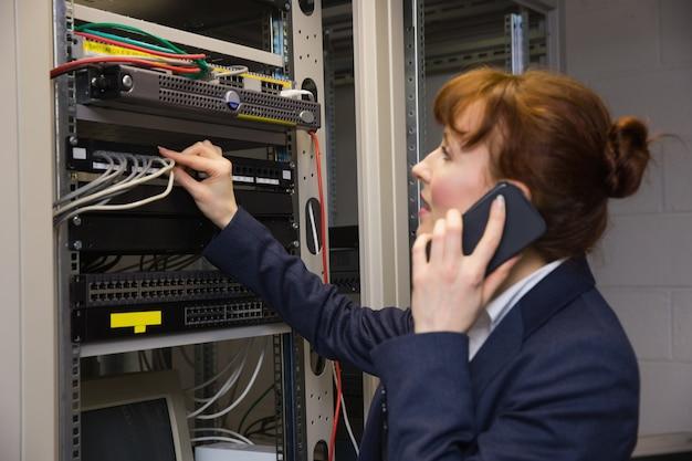 Hübscher techniker, der am telefon beim reparieren des servers spricht