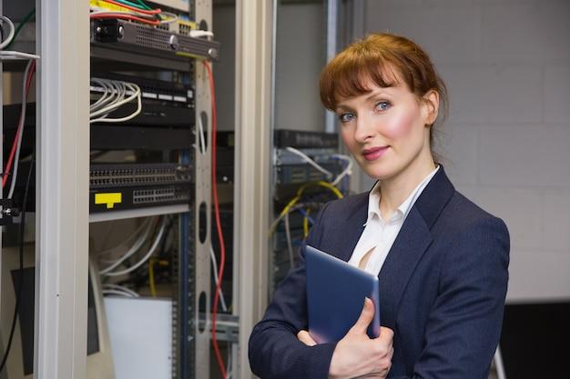 Hübscher techniker, der an der kamera neben dem offenen server hält tabletten-pc lächelt