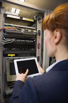 Hübscher techniker, der tabletten-pc beim reparieren des servers verwendet