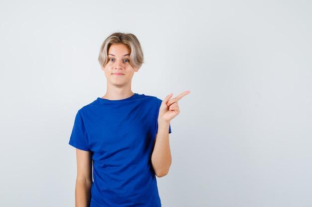 Hübscher teenager, der auf die obere rechte ecke im blauen t-shirt zeigt und hoffnungsvoll aussieht, vorderansicht.
