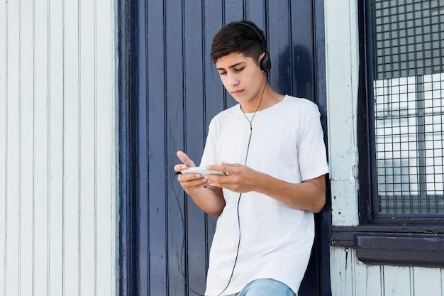 Hübscher teenager, der auf metallwand unter verwendung des smartphone und der hörenden musik sich lehnt