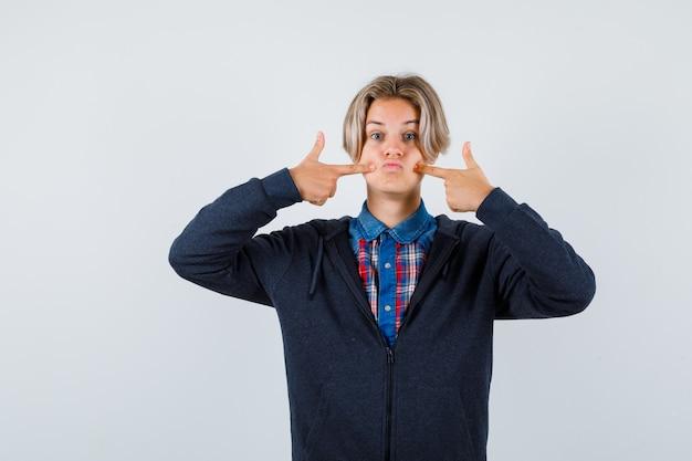 Hübscher teenager, der auf seine geschwollenen wangen in hemd, hoodie zeigt und verwirrt aussieht. vorderansicht.