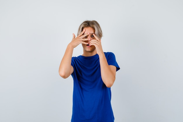 Hübscher teenager, der im blauen t-shirt durch die finger späht und verängstigt aussieht. vorderansicht.