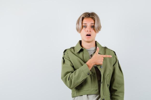 Hübscher teenager, der in grüner jacke nach rechts zeigt und erschrocken aussieht. vorderansicht.